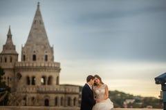 Giovani belle coppie alla moda le persone appena sposate che si siedono dal bastione del pescatore a Budapest, Ungheria fotografia stock libera da diritti