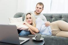 Giovani belle coppie che riposano sullo strato e sul video online di sorveglianza da un computer portatile nel salone fotografia stock libera da diritti
