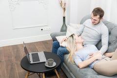 Giovani belle coppie che riposano sullo strato e sul video online di sorveglianza da un computer portatile nel salone immagini stock