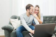 Giovani belle coppie che riposano sullo strato e sul video online di sorveglianza da un computer portatile nel salone immagine stock libera da diritti