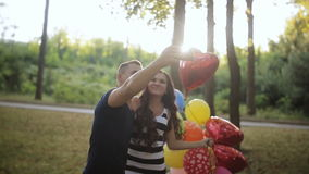 Giovani belle coppie che sorridono, facendo selfie, sedentesi nel parco della città video d archivio