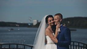 Giovani belle coppie che stanno sulla banchina del fiume e che abbracciano nel loro giorno delle nozze Persone appena sposate che stock footage