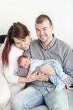 Giovani belle coppie con il nuovo bambino a casa fotografia stock