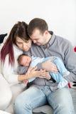 Giovani belle coppie con il nuovo bambino a casa immagini stock libere da diritti