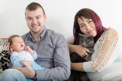 Giovani belle coppie con il nuovo bambino a casa fotografie stock