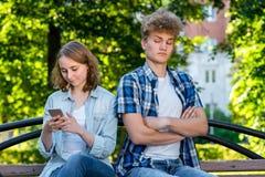 Giovani belle coppie In natura del parco di estate Si siedono su un banco La ragazza corrisponde nelle reti sociali Il tipo è Fotografia Stock