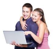 Giovani belle coppie sorridenti che esaminano computer portatile Fotografie Stock Libere da Diritti
