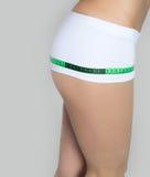Giovani belle coscie e gambe atletiche di misure della ragazza che misurano nastro, stile di vita sano, forma fisica, esercizio,  Fotografia Stock Libera da Diritti