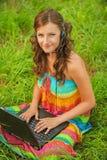 Giovani belle cuffie del computer portatile della donna Immagine Stock Libera da Diritti