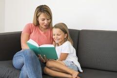 Giovani belle e donne felici che si siedono insieme ai suoi 7 anni adorabili della ragazza del libro di lettura biondo adorabile  Fotografia Stock