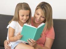 Giovani belle e donne felici che si siedono insieme ai suoi 7 anni adorabili della ragazza del libro di lettura biondo adorabile  Immagine Stock Libera da Diritti