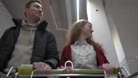 Giovani belle passeggiate dell'uomo e della donna attraverso il supermercato vista dal carrello archivi video