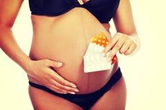 Giovani belle pillole della tenuta della donna incinta Fotografie Stock