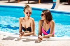 Giovani belle ragazze che sorridono, parlare, rilassantesi nella piscina Fotografia Stock Libera da Diritti