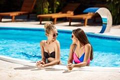 Giovani belle ragazze che sorridono, parlare, rilassantesi nella piscina Immagine Stock