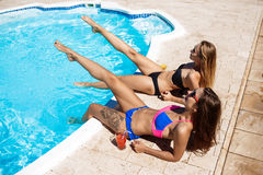 Giovani belle ragazze che sorridono, prendere il sole, rilassantesi vicino alla piscina Fotografie Stock Libere da Diritti