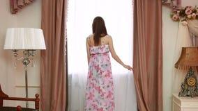 Giovani belle tende di apertura della donna in una camera da letto video d archivio