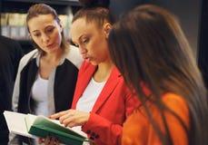 Giovani in biblioteca che esamina insieme un libro Fotografia Stock Libera da Diritti