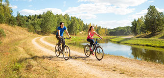 Giovani biciclette felici di guida delle coppie dal fiume Immagine Stock Libera da Diritti