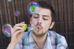 Giovani bolle felici di sapone e dell'uomo Fotografia Stock Libera da Diritti
