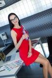 Giovani businesslady attraenti in vestito rosso si siedono sulla tavola nell'ufficio Fotografia Stock