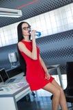 Giovani businesslady attraenti in vestito rosso si siedono sulla tavola nella bottiglia di acqua della tenuta e dell'ufficio Immagine Stock
