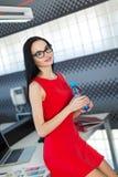 Giovani businesslady attraenti in vestito rosso si siedono sulla tavola nella bottiglia di acqua della tenuta e dell'ufficio Fotografia Stock Libera da Diritti