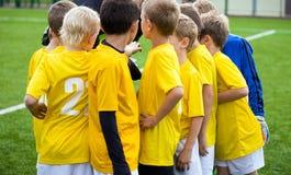 Giovani calciatori di calcio con l'allenatore La vettura motiva il gruppo di sport dei bambini Immagini Stock Libere da Diritti