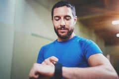 Giovani calorie bruciate d'inseguimento sorridenti dell'atleta sull'applicazione astuta elettronica dell'orologio dopo la buona s Fotografia Stock Libera da Diritti