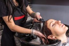 Giovani capelli di lavaggio del parrucchiere del cliente femminile con capelli tinti Immagini Stock