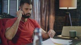 Giovani cattive notizie di udienza dell'uomo di affari che parlano sul telefono in Ministero degli Interni alla sera video d archivio