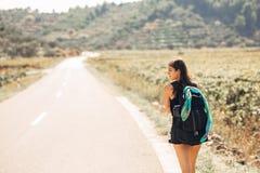 Giovani che backpacking donna avventurosa che fa auto-stop sulla strada Volume di viaggio degli zainhi, elementi essenziali d'imb Fotografia Stock