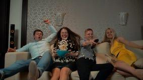 Giovani che cadono giù sul sofà per guardare TV con il cereale di schiocco video d archivio
