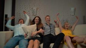 Giovani che cadono giù sul sofà per guardare TV con il cuscino o il cuscino archivi video