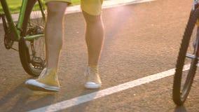 Giovani che camminano con le biciclette archivi video