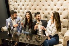 Giovani che celebrano e che tostano con il vino bianco Immagine Stock