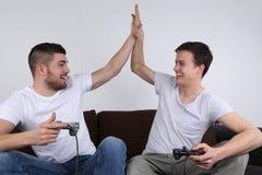 Giovani che danno livello cinque mentre giocando i video giochi Fotografia Stock