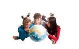 Giovani che esaminano globo (isolato su bianco) Fotografia Stock Libera da Diritti