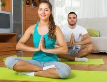 Giovani che fanno yoga dell'interno immagine stock libera da diritti