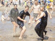 Giovani che giocano nello stagno del fango immagini stock