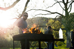 Giovani che hanno barbecue fuori nel giardino sulla festa del lavoro Immagini Stock Libere da Diritti