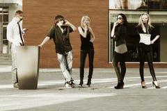 Giovani che invitano i telefoni Immagini Stock