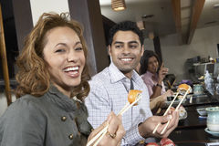 Giovani che mangiano i sushi con i bastoncini in ristorante fotografia stock libera da diritti