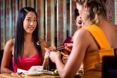 Giovani che mangiano i sushi in ristorante Fotografia Stock