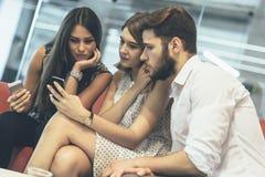Giovani che per mezzo dei loro telefoni cellulari Immagini Stock Libere da Diritti