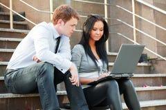 Giovani che per mezzo del computer portatile Fotografie Stock Libere da Diritti