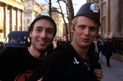 Giovani che portano i cappelli della polizia, Londra Immagini Stock