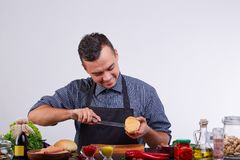 Giovani che producono hot dog nella cucina Ingredienti per il hot dog Fotografie Stock Libere da Diritti