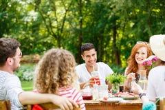 Giovani che ridono e che mangiano fotografia stock libera da diritti