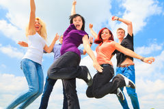 Giovani che saltano davanti al cielo blu Fotografia Stock
